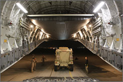 Airmen unload a Mine Resistant Ambush Protected vehicle from a C-17 aircraft in Baghdad.