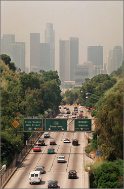 Traffic drives toward downtown Los Angeles on the 110 freeway as a curtain of smog shrouds the skyline.