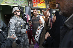 Iraqis gather around Sgt. Joseph Franklin to ask him about a clinic in Toma, a Baghdad neighborhood. An increased troop presence in the communities is part of a broader counterinsurgency strategy implemented this year.