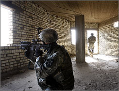 Sgt. Joseph Franklin and Pfc. Jonathan Burton search for explosives in the Toma neighborhood in southern Baghdad.