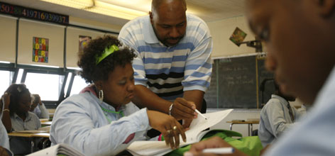 "Principal Jeffrey Robinson helps Ciera McAllister, 17, with class work at Baltimore Talent Development High School. ""One of the reasons innovative schools tend to perform higher is directly related to our autonomy to tailor our programs to match the needs of the majority of our students,"" Robinson says."