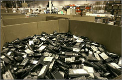 A box of analog cellphones in this 2003 file photo await refurbishing and recycling. In Feb. 2008, cellular carriers will be able to shut down analog cellphone networks.