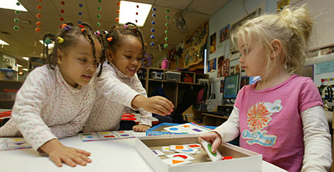 Athalia and Dora Marie Groelsema, both 4, play a matching shapes game with Madalin Chasles, right, in the pre-k program at Greenbelt Children's Center, in Greenbelt, Md. The private pre-school near Washington gets $100,000 annually from the state of Maryland.       PHOTO GALLERY