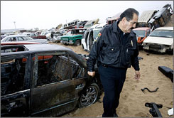 A police commander walks among stolen cars recovered by local police in San Luis Rio Colorado, Mexico, just south of San Luis, Ariz. Police say an average of 12 cars a month are stolen in the Arizona border town of 15,000 people.