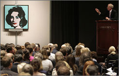 An auctioneer takes bids on Andy Warhol's 'Liz' during the post-war and contemporary art auction at Christie's in New York on November 13. The Warhol was sold for $21 million dollars.