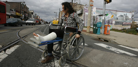 Blaine Straub, 25, of Philadelphia, pushes her wheelchair across trolley tracks in Philadelphia.  Straub, a cabinetmaker before she injured her leg, says it's been challenging to reach the local supermarket. &quot;If the only store available is down some dark street all torn up, it's not acceptable to a lot of women.&quot;