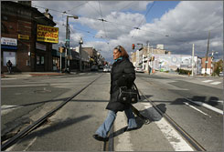 Tonyetta Demby, 38, of Philadelphia, pulls her cart across the same trolley tracks at 40th Street and Lancaster Avenue.