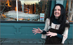 Cynthia Beal discusses life and death in front of her storefront window, which displays her very own biodegradable coffin in Portland, Ore.