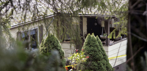 A covered porch on the side of a home surrounded by police tape is seen at the scene where six people were found dead in Carnation, Wash., Wednesday. Sgt. Jim Laing said the bodies were discovered about 8 a.m. by someone who knows the family.