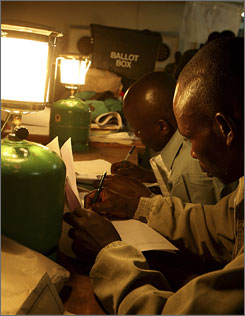 Election officials count votes using pressure lamps in Kisumu, Kenya.