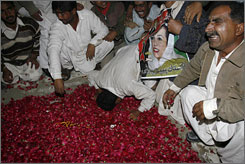 Supporters of former Prime Minister Benazir Bhutto mourn over her grave on Friday in Gari Khuda Bux, Pakistan.