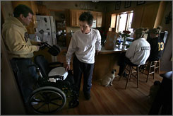 Coulter helps wife, Paula, ease into a wheelchair on the afternoon she arrived home after her extended recovery from serious injuries suffered during the I-35W bridge collapse.