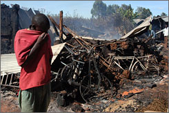 A man wipes his face in front of a church where dozens of people were burned alive in Eldoret, Kenya, Tuesday. Post-election feuding between tribes has killed hundreds since Friday.
