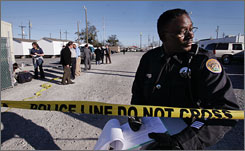 A New Orleans police officer stands at the crime scene in a FEMA trailer park where an officer was shot in March of 2007. The city's homicide rate jumped 30% in 12 months.