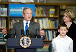 "President Bush, flanked by Secretary of Education Margaret Spelling and 6th grader Mariano Ramos, 11, defends the ""No Child Left Behind"" act during a visit to Horace Greeley Elementary School in Chicago."