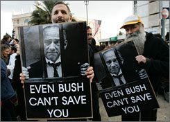 With a backdrop of the American flag waving in anticipation of Bush's trip to the Mideast, demonstrators hold placards depicting Israeli Prime Minister Ehud Olmert behind bars  a comment on an ongoing police investigation into corruption.
