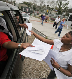 A Corps of Engineers employee, right, accepts claims as people hurried to beat last February's deadline to submit claims for damage from the flooding in the aftermath of Hurricane Katrina in New Orleans.
