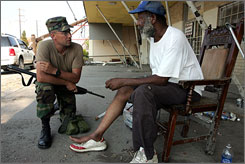 A member of the National Guard assists a New Orleans man in September 2005. The man could not walk and wanted to go to a hospital.