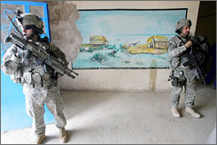 U.S. oldiers from the 4th Battalion, 64th Armor Regiment, secure a building as their commanders meet with local chiefs in Baghdad.