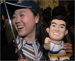 A Nationalist supporter displays a doll of presidential hopeful Ma Ying-jeou, as party members in Taipei celebrate their election victory.