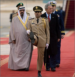 Saudi Arabia's King Abdullah and President Bush inspect an honor guard during a welcome ceremony upon for Bush at the King Khalid International Airport on Monday.
