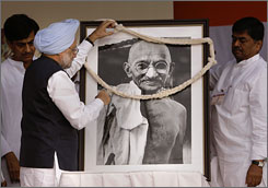 Indian Prime Minister Manmohan Singh garlands a portrait of Mahatma Gandhi on his 138th birth anniversary, in New Delhi, India, on Oct. 2, 2007.