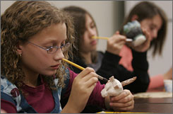 With renewed dexterity, Breanne paints a ceramic whistle she made in class.