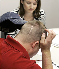 Army Spc. Bryan Malone, seen working with speech pathologist Sara Granberry last August, suffers from traumatic brain injury.