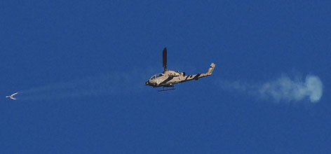 An Israeli attack helicopter fires a missile towards a target inside the Gaza Strip, south of the Karni crossing between Israel and Gaza, Tuesday. While violence escalated around the Gaza strip today, Israel test-fired a new long-range missile, capable of carrying nuclear warheads &quot;extremely long distances.&quot;