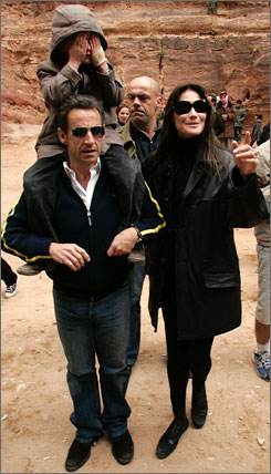 French President Nicolas Sarkozy, left, carries an unidentified child on his shoulders, as he walks with his new girlfriend, supermodel-turned-singer Carla Bruni, right, in Petra, Jordan.