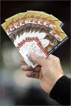 *A ticket scalper holds up tickets for the Cleveland Indians vs Minnesota Twins baseball game last summer. Ticketmaster lost Major League Baseball's resale business last year.