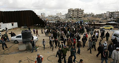 Palestinians cross the Rafah border into Egypt over a barrier destroyed by militants overnight.