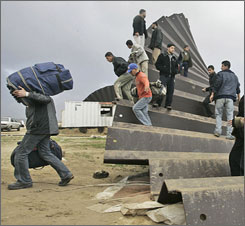 Gazans poured into Egypt to buy food, fuel and other supplies that have become scarce due to the blockade. Egyptian border guards and Hamas police took no action as Palestinians hurried over the border and began returning with bags of food, boxes of cigarettes and plastic bottles of fuel.
