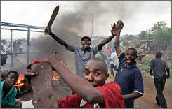 Men from Kenya's Luo tribe wield machetes and enforce a makeshift roadblock in Kisumu, on the main road to the Ugandan border, searching vehicles for Kikuyus trying to flee.