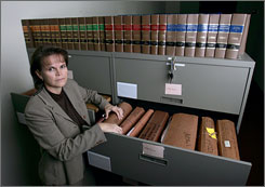 Cpl. Duwana Pelton with some of the cold case files in her office.