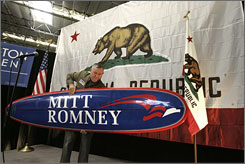 U.S. Congressman Dana Rohrabacher, R- Calif., carries a surf board for Republican presidential hopeful and former Massachusetts Gov. Mitt Romney during a campaign stop at Bassett Furniture in Fountain Valley, Calif., Thursday.