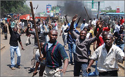 A mob of opposition supporters protest with makeshift weapons on the streets of Kisumu, Kenya, Thursday, following the shooting of Kenyan opposition lawmaker David Too by a police officer in Eldoret.
