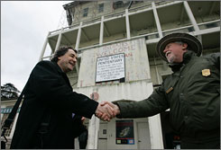 Da Vid, director of the Global Peace Foundation, left, shakes hands with National Park Service ranger Dave McDonald, right, during a visit to Alcatraz Island in San Francisco on Jan. 29.