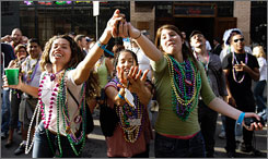 Left to right, Jemarie Kapparos, Zuna Portillo and Jami Grossi grab for beads Monday on Bourbon Street in the French Quarter of New Orleans.