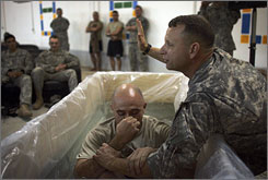 An Army chaplain prepares to perform a baptism for a fellow soldier during a Sunday service held at their post near Baghdad.