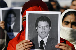 A member of the Solidarity Party of Afghanistan holds a picture of condemned journalist Sayed Parwez Kaambakhsh during a demonstration against his death sentence outside the United Nations office in Kabul on Jan. 31.