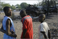 Young boys look at the remains of a burned tank  in the streets of N'Djamena, Chad, Wednesday. The  oil-rich central African nation saw battles between rebels and government forces over the weekend leaving corpses littering the streets and forced thousands to flee N'Djamena.