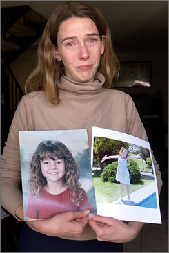 Erin Runnion holds up photos of her daughter, Samantha Runnion, then 5, one day after the little girl was abducted outside her home in Stanton, Calif., in July 2002.