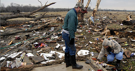Clay and Seavia Dixon pick through the debris of what is left of their home in Atkins, Ark., on Wednesday.