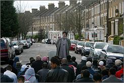 Islamic preacher Abu Hamza al-Masri, center, addresses followers before Friday prayers in London in April 2004.
