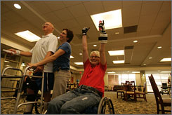 Stephanie Mezynski, right, cheers after making a strike while playing a match of bowling on Wii against Nathan Woodlief, left, as he gets assistance from occupational therapist Karen Ambrose, center, during a therapy session which utilizes the Wii for rehab, in Raleigh, N.C. in July 2007.
