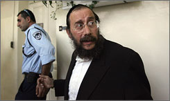 Abraham Mondrowitz, right, being escorted to an Israeli police officer in district court in Jerusalem in November 2007. An Israeli court has approved Mondrowitz's extradition to the United States on sex attack charges dating back to the 1980s. 