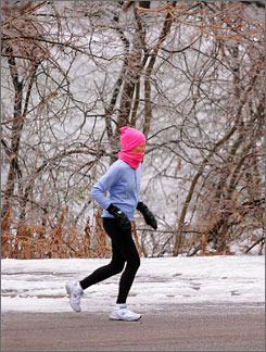 A woman runs along an icy road in Springfield, Ill., in December 2007.