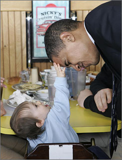 "Sen. Barack Obama, D-Ill., plays with Eric Hansen, 11-months-old, during a visit to Nicky's Cruisin' Diner Saturday in Bangor, Maine. Obama has taken caucus states ""very seriously,"" says his campaign manager."