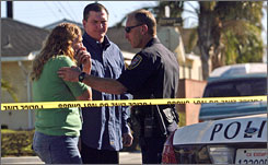 An Oxnard police officer speaks with parents outside E.O. Green Junior High School in Oxnard, Calif., after one student allegedly shot and wounded another on Tuesday.